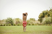 Boy in swimsuit walking in grassy field