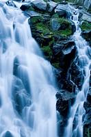 Waterfall rushing over rocky hillside