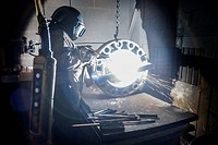 Worker cutting metal in foundry