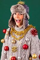 Hübsche junge Frau im grauen Pullover posiert begeistert lachend als geschmückter Weihnachtsbaum, lustige Studioaufnahme vor grünem Hintergrund. Prett...