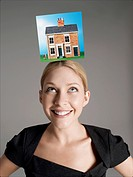 Model home on top of young woman´s head representing homeownership
