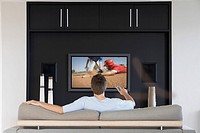 Back view of mid_adult man changing channels with television remote control in living room