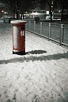 Traditional red english postbox at winter time snow