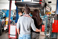 Rear view of young couple in garage