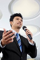 Businessman speaking into microphone