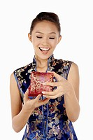 Woman in cheongsam holding Chinese decorated box
