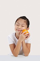 Girl smiling and holding an orange