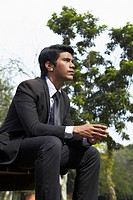 Young Asian businessman sitting on a park bench