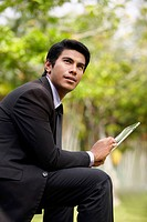 Young Asian businessman sitting on a park bench using a digital tablet