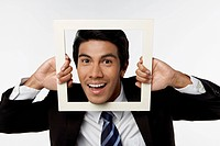Young businessman holding empty picture frame