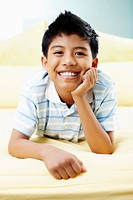 Boy lying forward in bed smiling