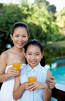 Mother and daughter with glasses of orange juice