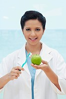 Female dentist brushing green apple with toothbrush