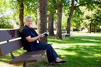 ESY-005484342 Woman reading book in a park