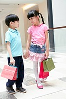 Boy and girl standing hand in hand and carrying shopping items