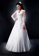 WR0992330 Fashionable young female brunette in white bridal dress posing