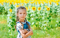 beautiful smiling little girl on sunflower field