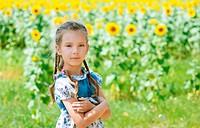 beautiful smiling little girl on sunflower field