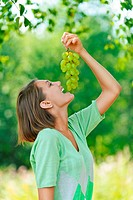laughing young woman eating grapes