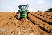Farm machinery preparing and planting a crop of potatoes in a field, Shottisham, Suffolk, England