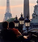 Rear view of couple sitting together in park near Place de la Concorde with Eiffel Tower at sunset in Paris