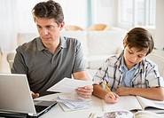 Father working on laptop and son (8-9) doing homework