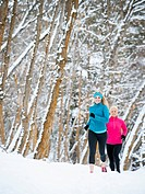 Two women jogging in winter forest
