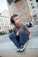 Boy sitting on curb, looking up