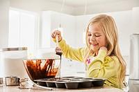 Girl (6-7) baking cupcakes