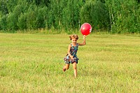 The girl plays with ball outdoors in sunlight