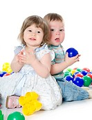 The little girl and boy plays multi-coloured balls isolated