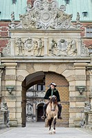 Frederiksborger with rider in historic costume trotting through a gate of Frederiksborg Palace, Danmark