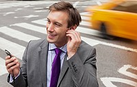 Businessman talking on cell phone on city street