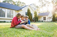 Caucasian boys using digital tablet on lawn