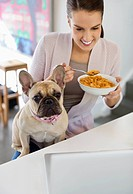 Woman eating cereal with dog on lap