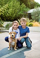 Smiling children petting dog outdoors