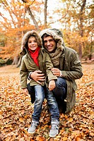 Father and son standing in autumn leaves