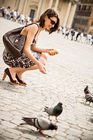 Caucasian woman feeding pigeons in town square