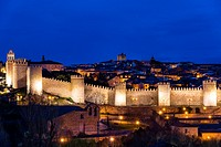 View from Cuatro Postes over the medieval city walls illuminated at night, Avila, Castile and Leon, Spain