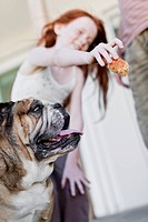 Girl giving dog biscuit