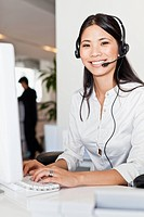 Businesswoman wearing headset at desk