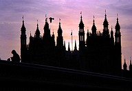 Street vendor on Westminster Bridge with the Houses of Parliament in the background caught in the rather disturbed light of a Winter dusk in London, E...