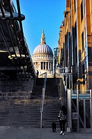 View of St. Paul's Cathedral from the banks of the River Thames by the Millenium Bridge (seen on the left-hand side) including street vendor on Peter'...
