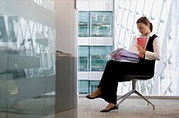 Businesswoman reading files in chair