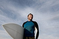 Surfer carrying board outdoors
