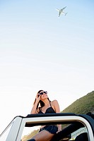 Woman sitting on roof of jeep on beach