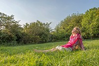 Girl sitting in grassy field