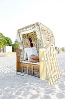 Young woman, 20+, relaxing in a roofed wicker beach chair on the beach, detail with legs, lifestyle, lightness, Niendorf at the Baltic Sea, Schleswig-...