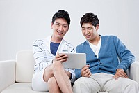 two men sitting on a couch sharing tablet PC