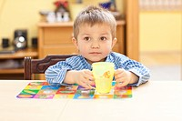 Little boy sitting at dinner table, drinking water from baby cup.